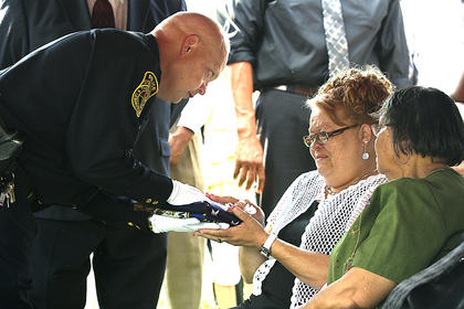 Assistant Chief Wally Brady hands an American flag to Joe Bell's fiance, Susan Yocum. Also pictured is Yocum's mother.