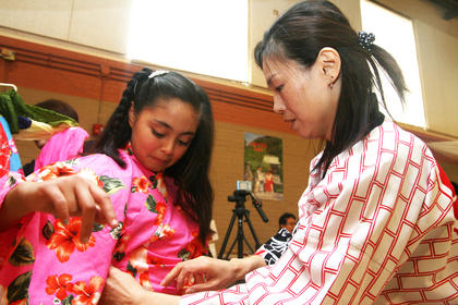 Hitomi Ogasawara helps Aleli Huerta, 11, put on a kimono.
