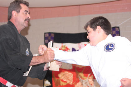 Andrew Tungate punches through a wooden board during a martial arts demonstration by students at John Cox Martial Arts.