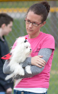 Shown is Melissa Mattingly with her primped pup snug in her arms.