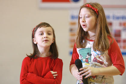 First-grade Livia Goff, left, and second-grader Maggie Coffman sing &quot;Brand New Key.&quot;