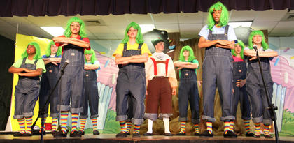 The Oompa-Loompas sing a song about overeating as they escort Augustus Gloop (Chase Lancaster) from the factory.