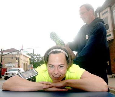 Kim Higdon of Springfield enjoys some assisted stretching thanks to Tom Robey before the Pokey Pig 5K.