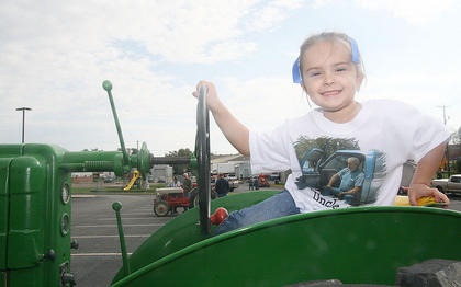 "Josie Mattingly takes the driver's seat in a John Deere MT during the antique tractor show. She wore a shirt in memory of her ""Uncle Jim"", who died a few weeks ago."