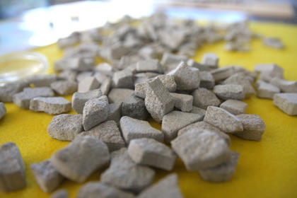 Pieces of limestone were chipped away from the bench to reveal the designs. The pieces were used to create necklaces for students at Lebanon Elementary School.