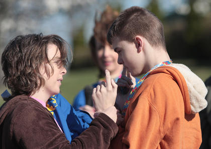 Kim Nelson places a medallion around the neck of her son, Blake Forbis.