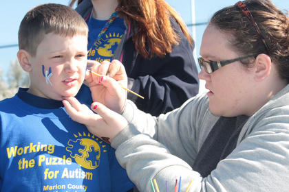 J.T. Lee, 8, has his face painted by Ann Courtney Caldwell.