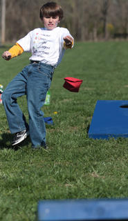 Jacob Benningfield, 7, tries his hand at cornhole.