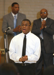 Malik Dorsey of the Young Men of Faith sings. Rev. Dale Smith and Rev. Ricco Floyd stand and clap along in the background.