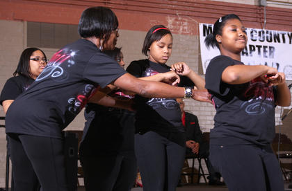 Mary Cowherd helps members of the step team from the Marion County Youth Center before they perform during the Black History Celebration Feb. 27 at Centre Square in Lebanon.