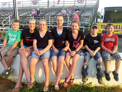 Pictured, from left, are Cameron Pittman, Lindsey Browning, Morgan Pittman, Adrienne Thomas, Kaley Thomas, Peyton Thomas and Cage Thomas pose for a photo at the Adair County Fair before watching Logan and Austin Pittman drag race.