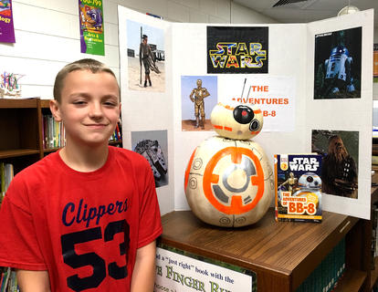 """West Marion Elementary School student Carter Leake is pictured with his BB-8-themed pumpkin from""""Star Wars Adventures of BB-8"""" book."""