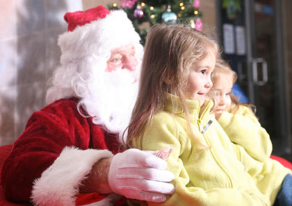 Twins Bradi and Brinna Hawkins, 4, of Lawrenceburg pose for a photo with Santa.