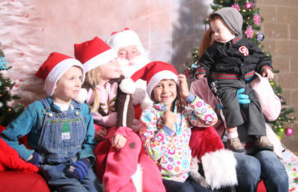 The Robbins family gets ready for a photo with Santa. From left, they are Connor, Olivia, Addison and Jameson, who is being held up by mom, Megan. They were in town from Rxxx Air Force Base in Georgia.
