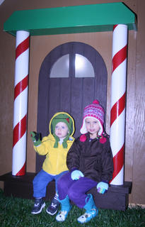 Connor, 17 months, and Chloe Cox, 5, take a break in the doorway of a small house.