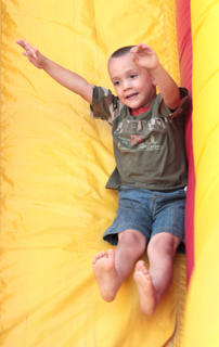 Jonny Sprowles, 3, slips down the slide.