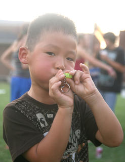 Camden Adams, 5, has fun with a whistle he won during the Marion County Public Library's Cinema at the Square Friday at Centre Square.