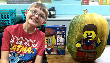 """West Marion Elementary School student Clayton Gribbins is pictured with his """"Emmet's Guide to Being Awesome"""" pumpkin."""