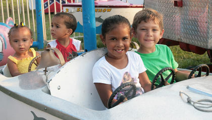 From left, Deshaila Brown, 2, Cordelle Douglas, 2, Deshaila Newby, 5, and Peyton Young, 5, drove in circles on one of the  children's rides.