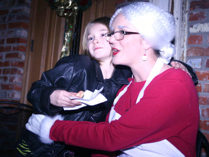 Elanna Chesser, 8, gives Mrs. Claus a hug.