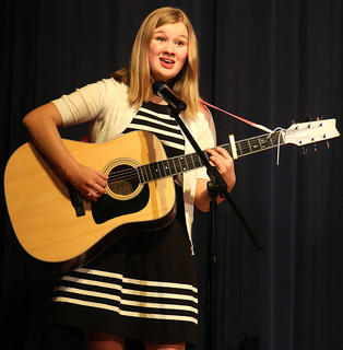 Jane Palagi plays the guitar and sings a Christmas song.