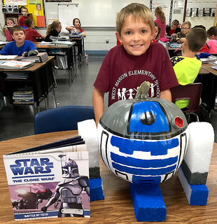 """West Marion Elementary School student Gavin Smith is pictured with his R2D2-themed pumpkin from the book""""Star Wars The Clone Wars."""""""