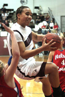 Sophomore Makayla Epps drives the ball to the basket against Nelson County defenders in the girls 5th Region seni-final game.