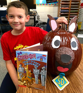 """West Marion Elementary School student Isaac Wright with his Scooby-Doo-themed pumpkin fromthe """"Shiny Spooky Knights"""" book."""