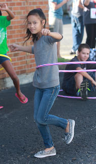 Lea O'Daniel, 7, fights to keep her hula hoop going while standing on one foot.