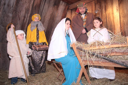 From left, shepherd (Jaxon Hood) and wise man (Cody Hood) gather around Mary (Kim Hood) and Joseph (Chad Hood). The angel is Shelby Hood.