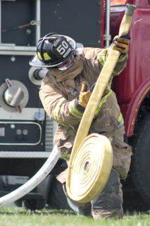 Mike Mullenhour of the Loretto Fire Department unrolls a fire hose at the start of the obstacle/relay challenge.