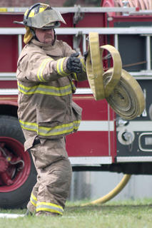 John Skaggs of the Raywick Fire Department unrolls the fire hose at the start of the obstacle/relay challenge.