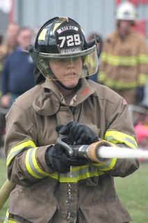Matthew Riggs aims the fire hose at softballs during the obstacle/relay challenge.