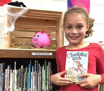 """West Marion Elementary School student Malia Sutphin is pictured with her Wilbur-themed pumpkin fromthe book """"Charlotte's Web."""""""