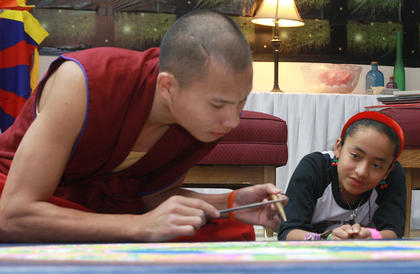 Julisa Hines, 12, of Lexington takes a close look while Penzin Dawa works on the mandala Thursday afternoon.