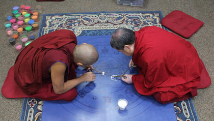 The monks started adding sand in a variety of colors to the mandala.