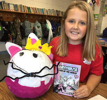 """West Marion Elementary School student Olivia Cecil is pictured with withher """"Baby Mouse Queen of the World"""" pumpkin."""
