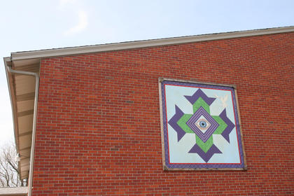 This &quot;God&#039;s Eye&quot; pattern hangs on the side of the former school building at St. Francis Xavier Catholic Church. 
