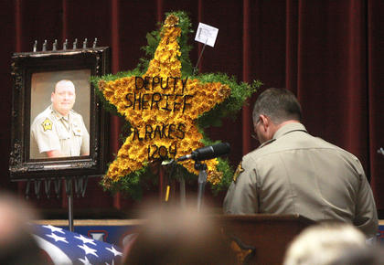 Marion County Sheriff Jimmy Clements walks past a photo of Deputy Anthony Rakes after speaking at Rakes&#039; funeral Saturday at Marion County High School. 
