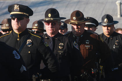 Law enforcement officers stand at attention during graveside services for Deputy Anthony Rakes.