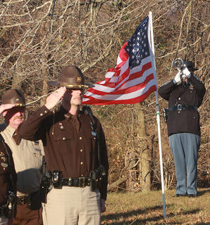 "A trumpeter plays ""Taps"" during graveside services for Deputy Anthony Rakes."