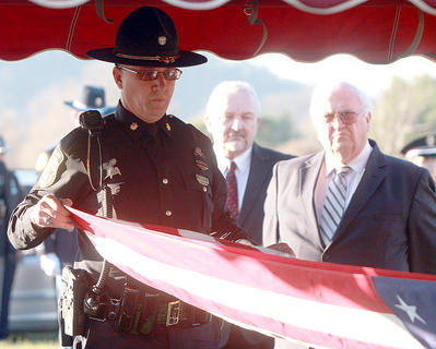 Major Greg Young folds the flag that was draped over Deputy Anthony Rakes coffin. The flag was presented to Rakes&#039; family.