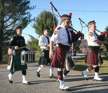 Bagpipers and drummers escort the hearse as it arrives at the Old Liberty Cemetery.