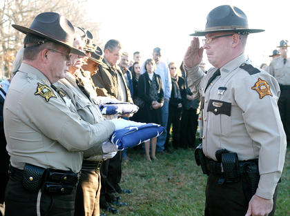 An American flag draped Deputy Anthony Rakes&#039; coffin. After it was folded, Adam Rainwater, right, of the Green County Sheriff&#039;s Department presented the flag to Marion County Sheriff Jimmy Clements.