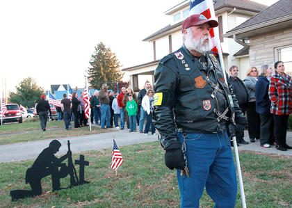 Ed Boots of Lexington, a member of the Patriot Guard Riders, holds up a flag in honor of Deputy Anthony Rakes outside of Bosley Funeral home during visitation Friday evening.