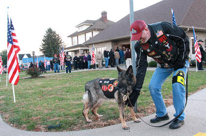 Jim Clendenning of the Kentucky Patriot Guard Riders pets Sgt. Beyco outside of the visitation for Deputy Anthony Rakes Friday at Bosley Funeral Home. Sgt. Beyco served with the U.S. Marines in Iraq, where she detected explosives.