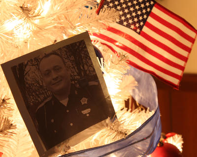 Shown is the tree dedicated to Sherriff's Deputy Anthony Rakes. It was adorned with Christmas decorations, photos of him, and American flags.