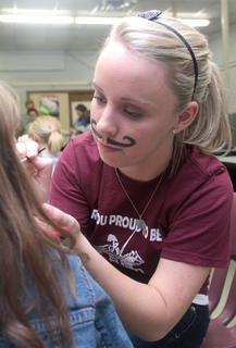 Rachel Bell, wearing a painted on mustache, did some face painting of her own.