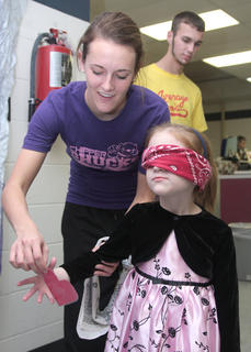 Andrea Luckett helps Morgan Schooling (blindfolded) prepare to Pin the Heart on the Body, a variation of Pin the Tail on the Donkey.