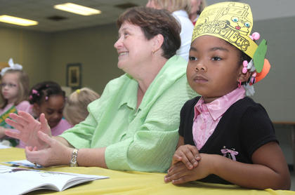 Young author Mikhia Gunn sits at a table with her kindergarten teacher Cindy Williams. Williams&#039; class wrote a book about safety that was available for purchase at Share-A-Story Night.